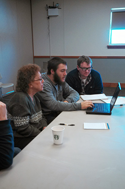 group of four people sitting at a conference table looking at a laptop