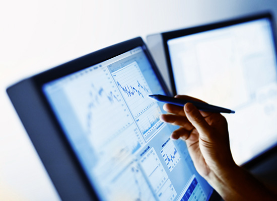 two computer screens showing graphs that someone is pointing to with a stylus