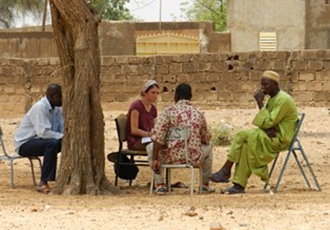 group of people sitting outside under a tree on fold up chairs